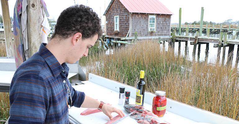 Harvest chef Tyler Kinnett cuts a banded rudder fish -- something he'd never heard of -- while visiting Abundant Seafood in South Carolina last year.