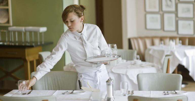 Waitress sets out water glasses in restaurant .jpg