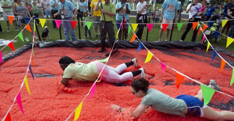 Competitors crawl through strawberry jelly