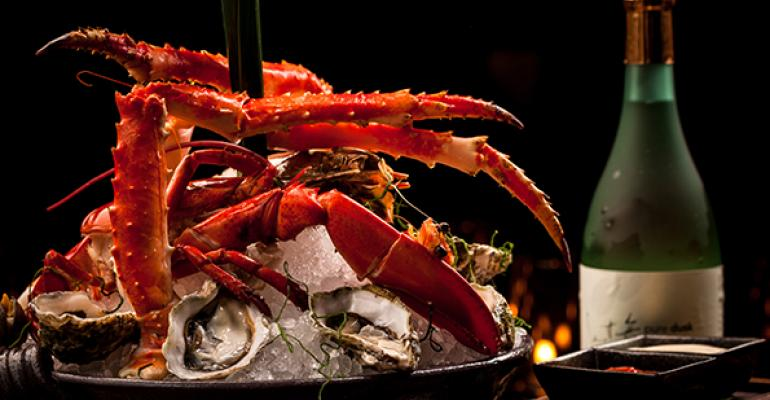 The Seafood Tower at Bacircoli Miami features one half of a cooked Maine lobster in the company of 6 raw kumamoto oysters a cooked jumbo shrimp 6 headon prawns 4 baby scallops 3 king crab legs and black steamed mussels over crushed ice