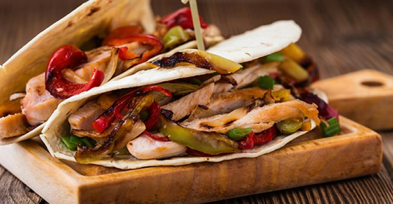 Chicken fajitas with grilled onions and bell peppers and serve with flour tortillas on a rural wooden board